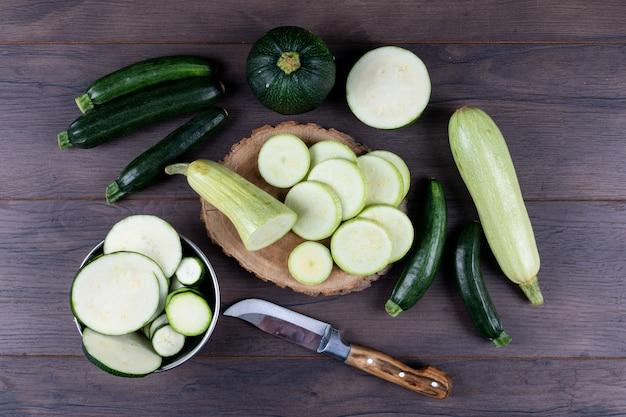 Juego de cuchillo y otros calabacines en un tazón y alrededor y rodajas de calabacines en una mesa de madera oscura. aplanada