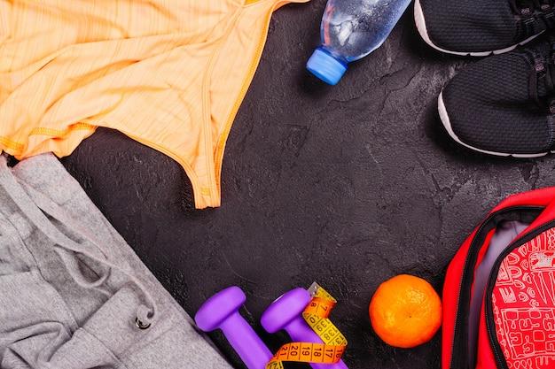 Juego de deporte o fitness con ropa femenina, mancuernas, bolso y calzado deportivo sobre fondo negro