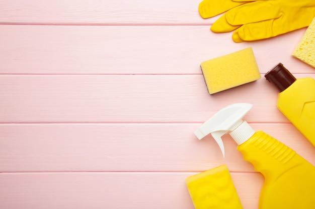 Juego de limpieza. herramientas amarillas para limpieza. agentes de limpieza, spray, guantes de goma sobre fondo de madera rosa. lay flat