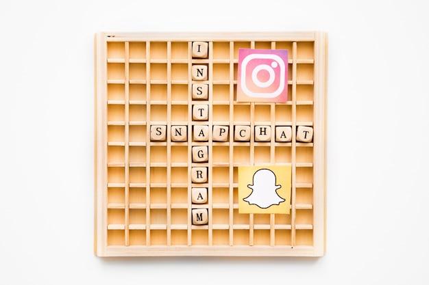 Juego de madera de scrabble que muestra palabras de instagram y snapchat con sus iconos