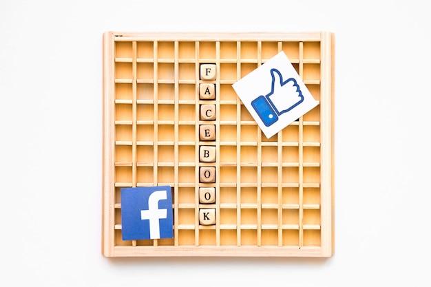 Juego de madera de scrabble con símbolo, palabra e icono de facebook