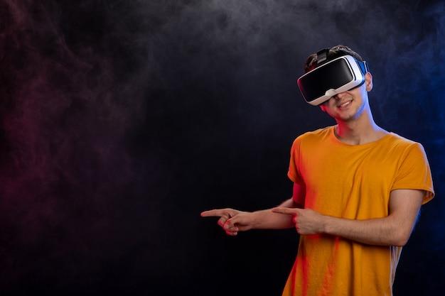 Juego masculino guapo en realidad virtual en superficie oscura