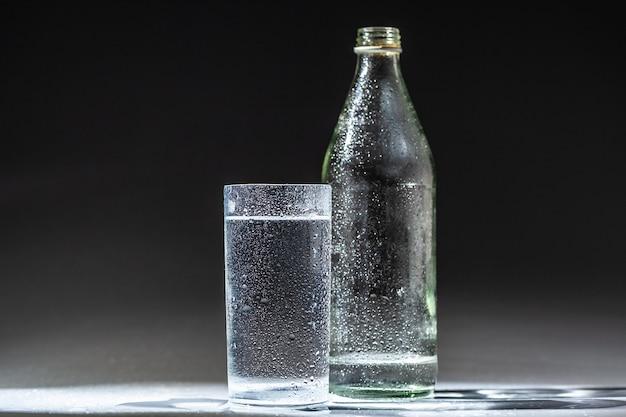 Juego de mesa servida de botella de agua mineral y vidrio