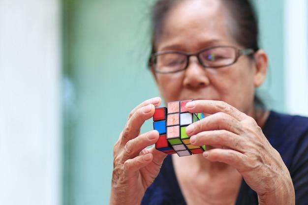 Juego de mujer mayor asiática o resolver el juego de cubo de rubik.