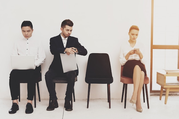 Juego de la mujer en el teléfono y sentado con compañeros de trabajo