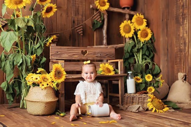 Juego de niña feliz entre girasoles florecientes cerca del banco. niño comiendo galletas con leche