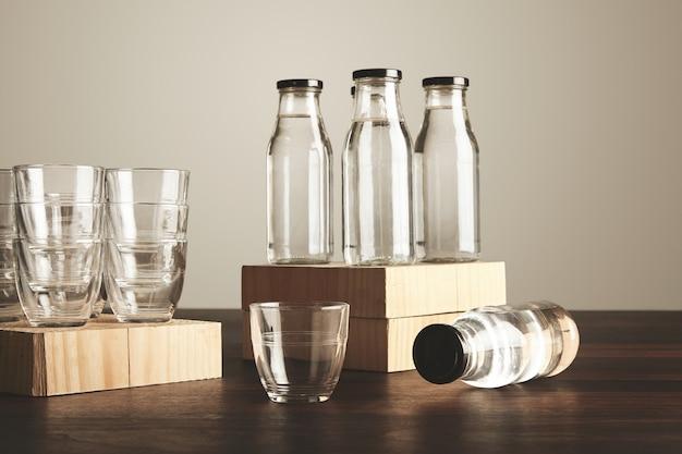 Juego perfecto de agua pura, limpia y saludable en botellas de vidrio transparente y vasos presentados en madera