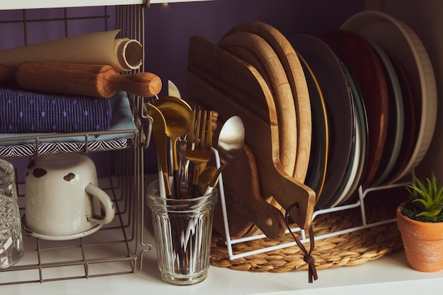 Un juego de platos y utensilios de cocina tabla de cortar platos en el estante utensilios de cocina platos