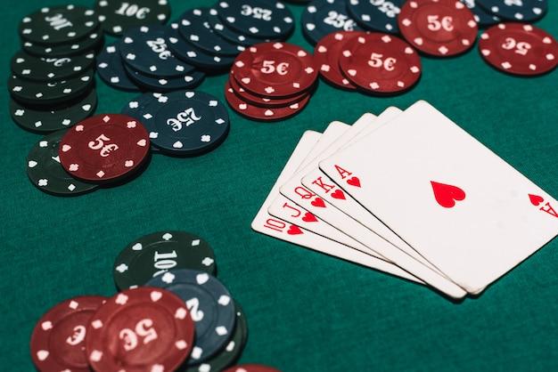 Juego de póker de casino y combinación ganadora. escalera real y una apuesta de fichas en la mesa