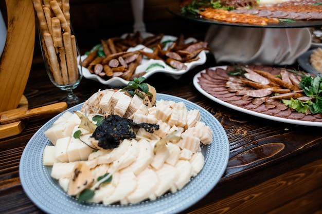 Juego de quesos, salchichas y bocadillos salados en la mesa de madera