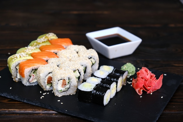 Juego de rollos de sushi con atún, salmón, pepino, aguacate sobre una mesa negra. primer plano, poca profundidad de campo. surtido de comida japonesa en restaurante.
