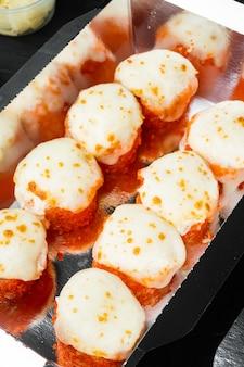 Juego de rollos de sushi en caja de comida de entrega, sobre mesa de piedra negra