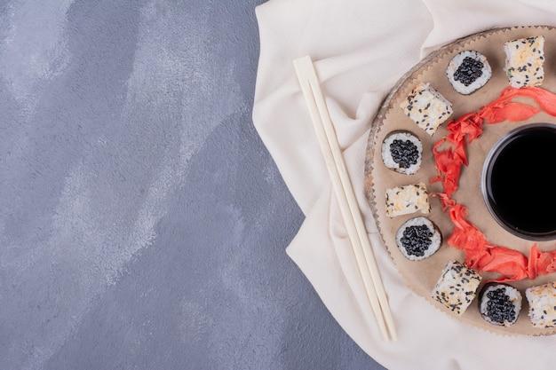 Juego de sushi. rollos de sushi maki y alaska en placa de madera con mantel, jengibre encurtido y salsa de soja.