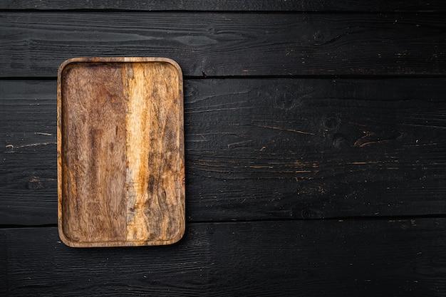 Juego de tabla de cortar de madera vacía, vista superior plana, con espacio para copiar texto o su producto, sobre fondo de mesa de madera negra
