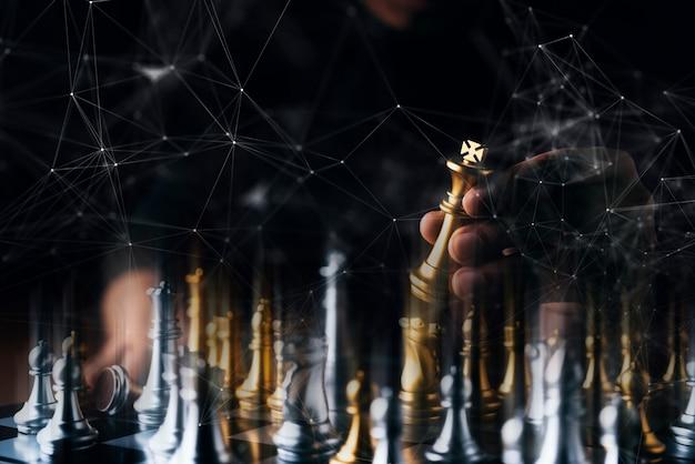 El juego de tablero de ajedrez de la estrategia de la estrategia empresarial con el fondo negro del tacto de la mano con el espacio libre de la copia para su texto