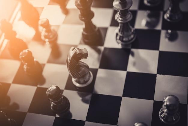 Juego de tablero de ajedrez de la estrategia de la estrategia empresarial con el fondo negro del tacto de la mano