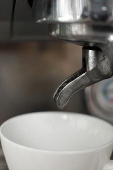 Juego de tazas blancas vacías en la máquina de café espera café recién hecho caliente
