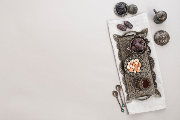 Juego de té árabe tradicional; nueces; fechas y té en bandeja metálica sobre fondo blanco