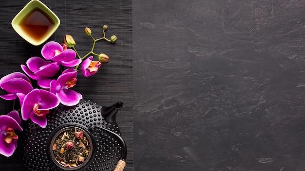 Juego de té asiático con flor de orquídea e ingrediente de té seco en mantelito negro