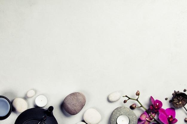 Juego de té asiático y piedras de spa sobre fondo de hormigón