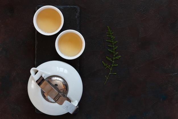 Juego de té asiático en porcelana blanca con leche verde oolong en el escritorio de piedra negra