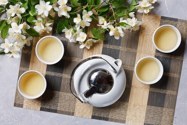 Juego de té asiático de la porcelana blanca con té verde y jazmín en la servilleta de bambú, visión superior.