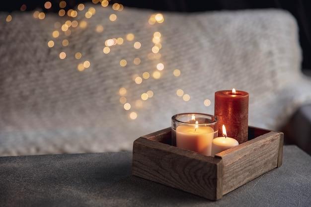 Juego de té blanco y tortas en mesa de madera gris. bandeja de madera blanca con tazas, tetera y guirnaldas de luces.