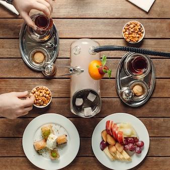 Juego de té con bocadillos dulces y frutas vista superior