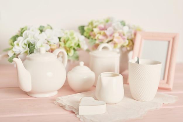 Juego de té y café sobre la mesa sobre un fondo blanco