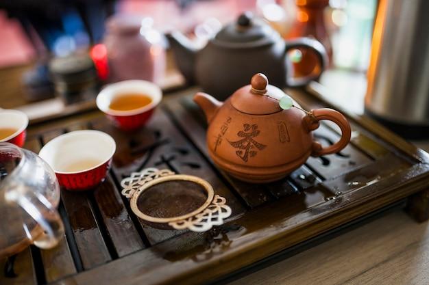 Juego de té chino con colador metálico en bandeja de madera.