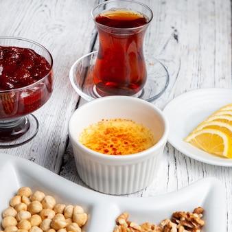 Juego de té, nueces, mermelada de frutas, limones en rodajas y delicioso postre en un plato sobre un fondo blanco de madera. vista de ángulo alto.
