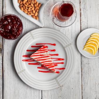 Juego de té, nueces, mermelada de frutas, limones en rodajas y delicioso postre en un plato sobre un fondo blanco de madera. vista superior.
