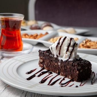 Juego de té, nueces y postre en un plato sobre un fondo blanco de madera. vista lateral.