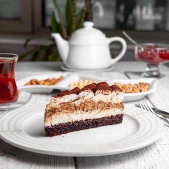 Juego de té, nueces, tetera, mermelada de frutas y delicioso postre en un plato sobre un fondo blanco de madera. vista lateral.