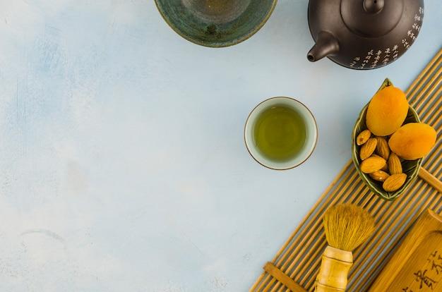 Juego de té oriental con pincel y frutos secos sobre fondo blanco