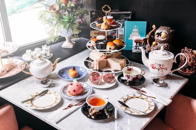 Juego de té de la tarde inglés que incluye té caliente, pastelería, bollos, sándwiches y mini tartas.