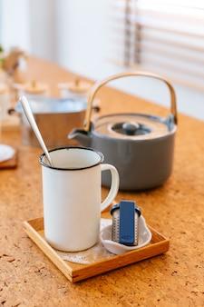 El juego de té de la tarde sirvió agua caliente en una olla gris con taza de lata e infusor de té.