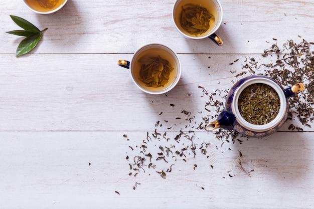 Juego de té tazas, tetera y té preparado con hojas secas en la mesa de madera blanca