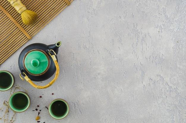 Juego de té tradicional con pincel en mantel sobre el fondo de hormigón gris