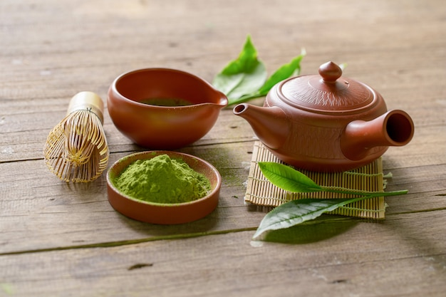 Juego de té verde matcha y té japonés. tetera de cerámica y una taza humeante sobre fondo de madera