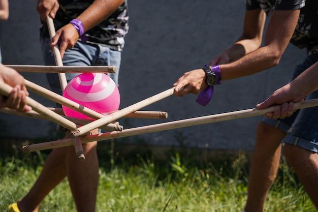 Juego de teambuilding para grupos de personas para fomentar el espíritu de equipo y aumentar la amistad de los compañeros. juego de equipo con pelota y palos.