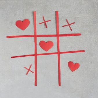 Juego de tic tac toe con adornos de corazones rojos.