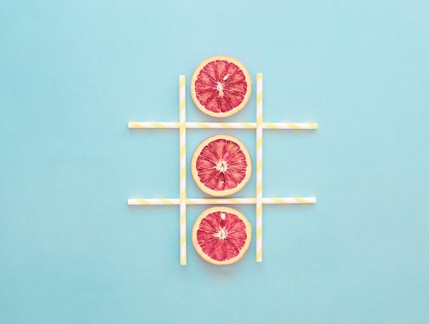 Juego de tic-tac-toe rebanada de naranja, concepto de verano saludable, azul claro, minimalismo