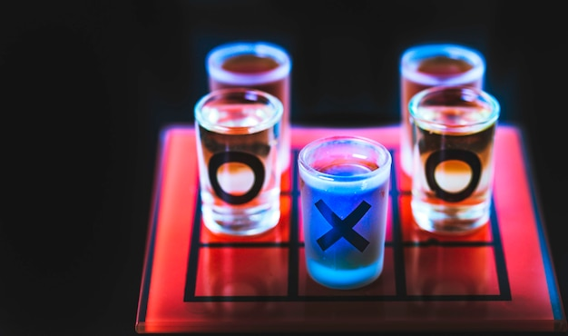 Juego de tic tac toe con vasos de chupito en azul.