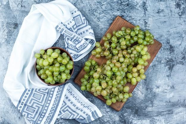 Juego de toalla de cocina y uvas verdes en un recipiente sobre yeso sucio y fondo de tabla de cortar. endecha plana.