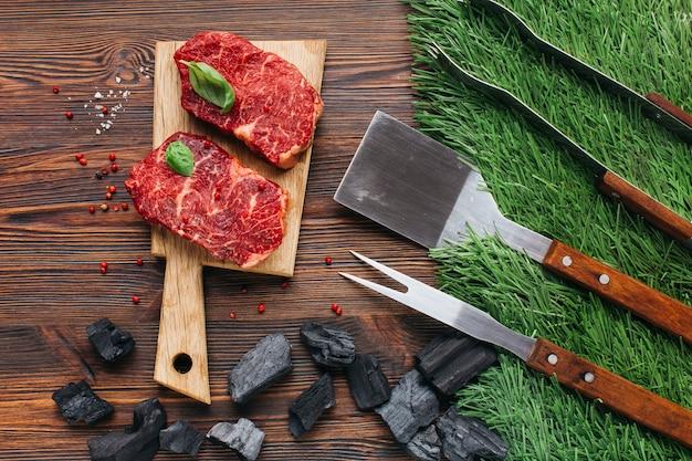 Juego de utensilios de barbacoa y carbón con filete crudo en mesa de madera