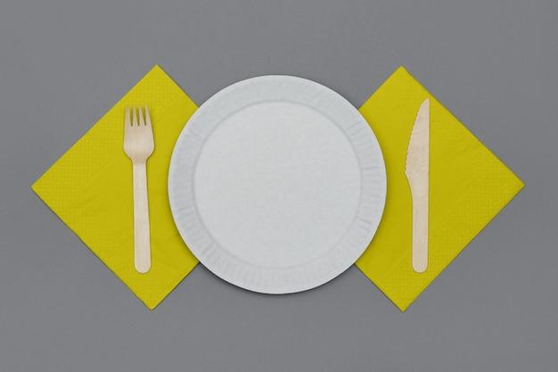 Juego de vajilla desechable ecológica de material natural. plato de papel blanco, tenedor y cuchillo de madera y servilletas amarillas sobre fondo gris, vista superior. concepto ecológico.