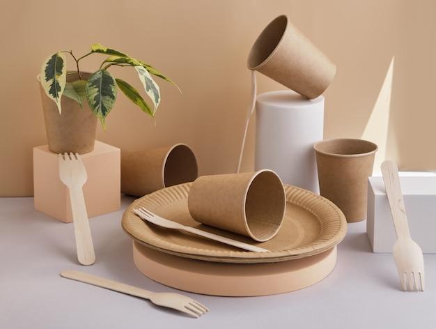 Juego de vajilla ecológica, tenedores de madera, platos y vasos colocados en modernos podios y pedestales geométricos.