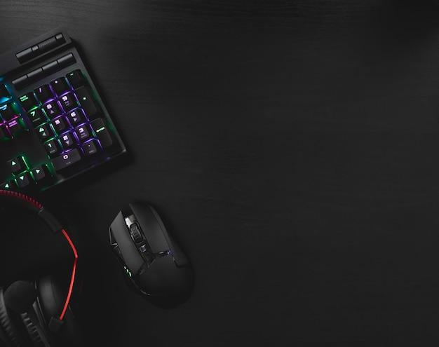 Juegue desde el concepto de hogar, vista superior de un equipo de juego, mouse, teclado, joystick, auriculares, joystick móvil, auriculares en la oreja y alfombrilla de ratón sobre fondo de mesa negro con espacio de copia.