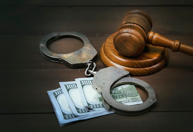 Juez gavel y esposas con billetes de dólares en la mesa de madera